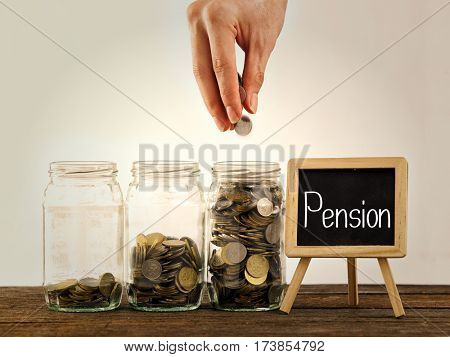 hand putting a coin into glass bottle, saving concept and a mini blackboard with text pension