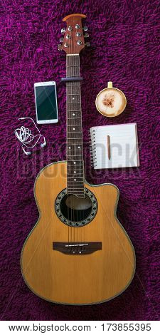 acoustic guitarsmartphonecup of coffee and blank notebook on purple carpet background