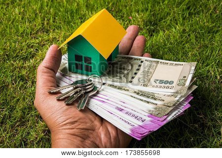 hand holding new indian currency notes or rupees 500 and 2000 and house model over green grass - indian real estate and finance concept