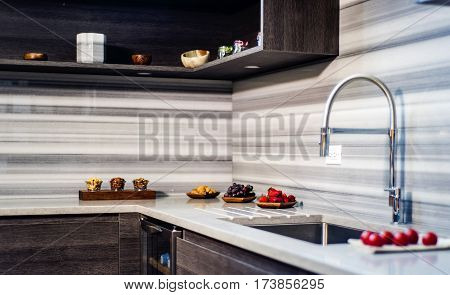 beautiful modern kitchen granite counter top, brown kitchen with a backsplash and granite counters, L shaped kitchen with a granite countertop and stainless steel sink