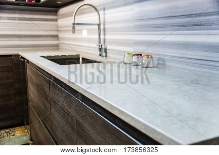 Brown kitchen cabinets. Modern base cabinets with granite kitchen countertop. Modern Cabinets. Contemporary Italian kitchen cabinet design. Stainless steel sink and faucet with wooden kitchen cabinet.