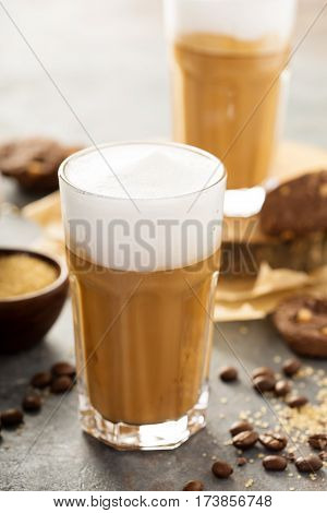 Hot latte with thick foam and chocolate syrup in tall glasses