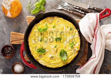 Potato and herbs fritatta in a cast iron pan
