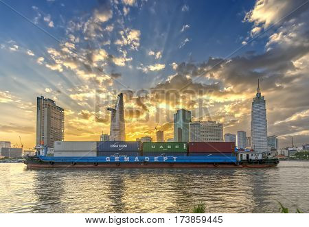 Ho Chi Minh City, Vietnam - February 14th, 2017: Beauty skyscrapers along urban river down smooth light when export transport ship passing show development in Ho Chi Minh City, Vietnam