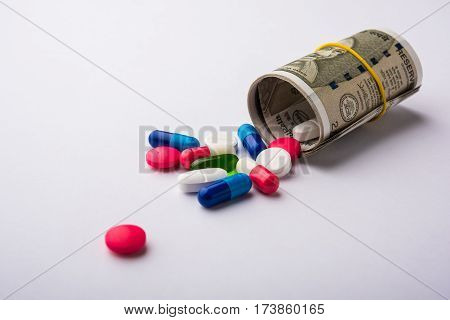 colourful Pills, capsules and tablets flowing from roll of indian new currency note of rupees 2000 or 500 on a white background, selective focus