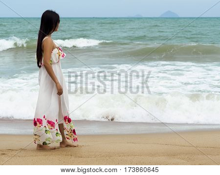 Young beautiful woman walking aline the seashore and looking at the sea. Summer time traveling tourism relaxation or vacations concept