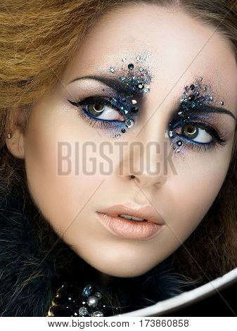 Beauty portrait of young woman with modern fashion makeup with rhinestones. Studio shot. Carnival or party makeup