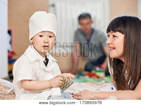 Cute little boy in medical uniform playing doctor with mother