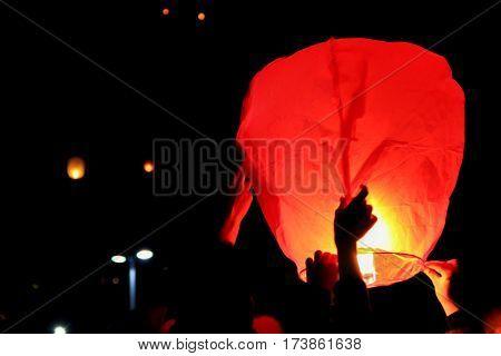 people releasing Skylanterns to sky at night