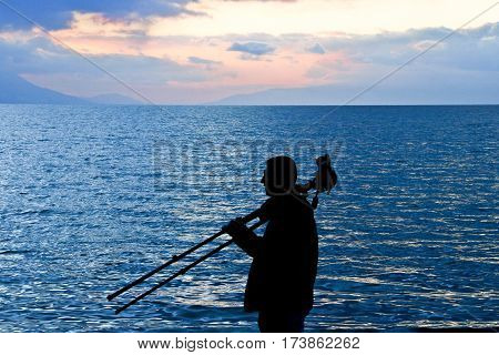 man silhoutte near the sea with camere