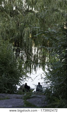 Lasalle, Quebec, October 4, 2015 -- Vertical of two people sitting by the waters edge with green trees and foliage framing them in Woodland Park in Lasalle, Quebec on a bright sunny day in October.