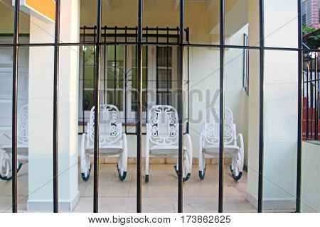 Facade with metal protection and grill windows with blurring of rocking chairs