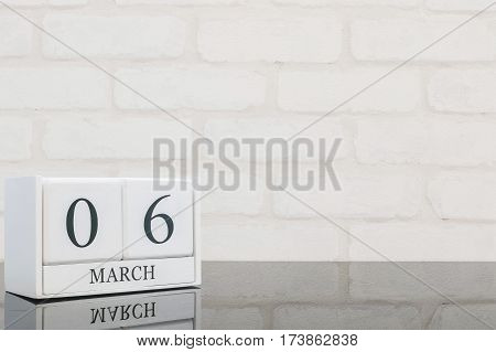 Closeup white wooden calendar with black 6 march word on black glass table and white brick wall textured background with copy space selective focus at the calendar