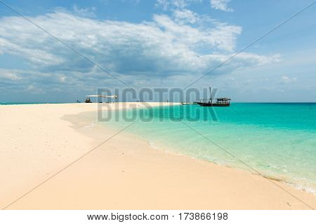 colorful view of Zanzibar beach and touristic boats in the ocean with horizon on the background