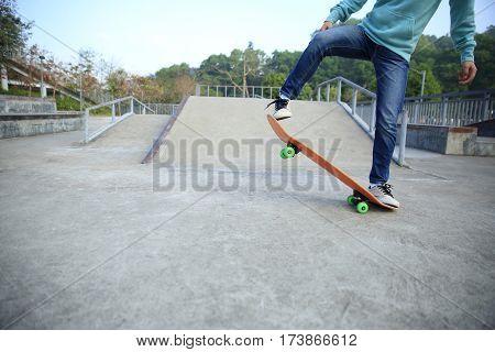 young skateboarder legs riding skateboard at skatepark ramp