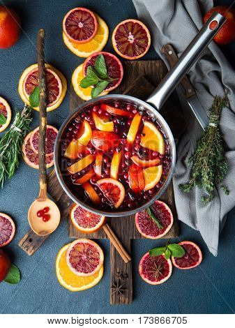 Mulled wine with slice of red orange, fresh rosemary and spices. Top view