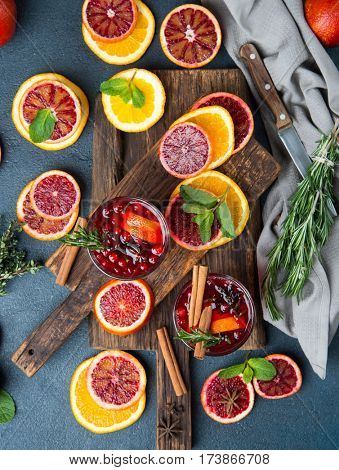 Mulled wine with slice of red orange, fresh rosemary and spices. Glass with hot drink, top view
