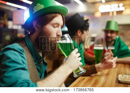 Young bearded man drinking green beer in pub