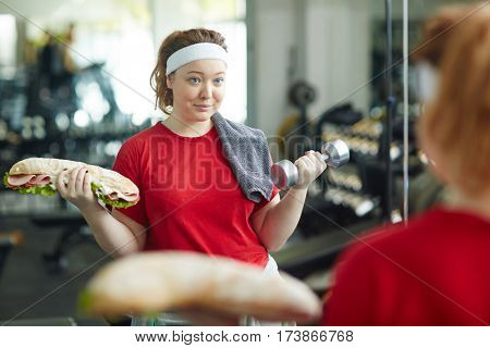Portrait of young overweight woman doing weight exercises with huge fat sandwich while working out in gym , struggle of dieting to lose weight