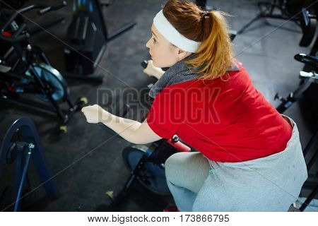 Above view portrait of obese sweaty woman determined to lose weight by working out on bicycle machine in gym
