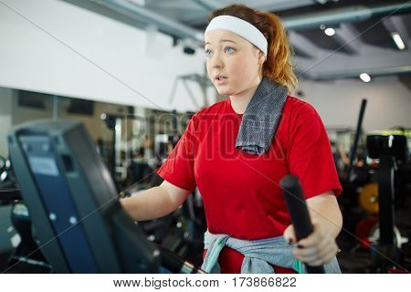 Cute overweight girl with red hair working out using machines in gym, dreaming to be thinner