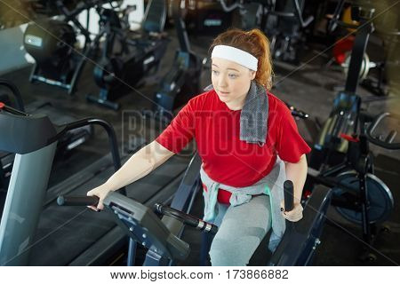 High angle portrait of cute overweight woman with red hair training using elliptical machines in gym