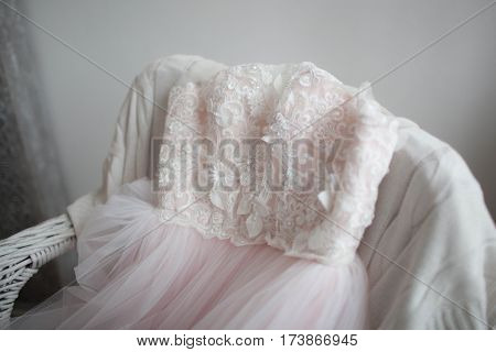 beautiful , pink , light gown of tulle and lace, lying on the chair wedding concepts
