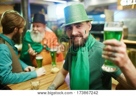 Young man in costume of leprechaun toasting with green beer