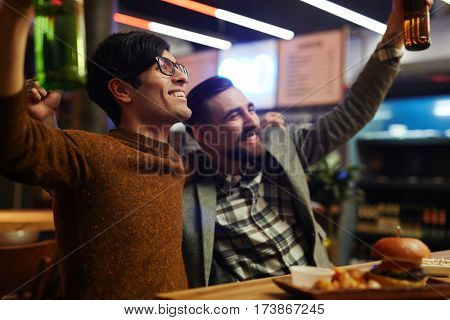 Joyful buddies toasting for victory of their favorite football team