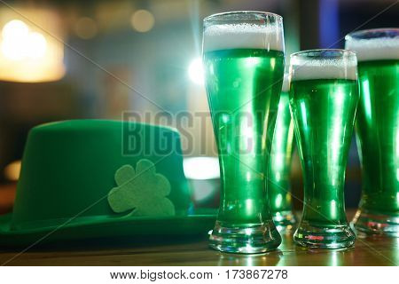 Three glasses of green beer and hat with shamrock leaf near by
