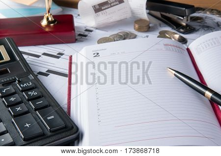 The business accessories notebook calculator fountain pen and graphics tables charts on a wooden office desk.