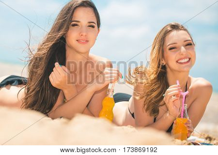 Gierlfriends drinking cold drink beverage having fun at beach party. Female babes in bikini enjoying orange water from glass boutle. summer concept