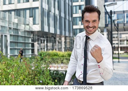 Portrait of cheerful businessman with clenched fist standing outside office building