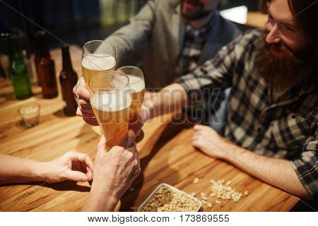 Bearded buddies toasting with beer in pub