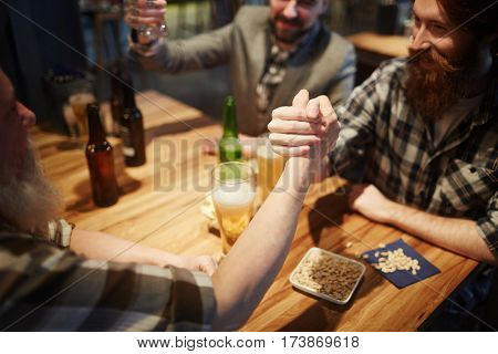 Young and senior men having wrestling competition on pub table