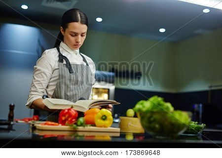 Young woman with cookery book preparing food at home