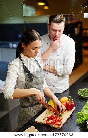 Trainee preparing slow food under chef control