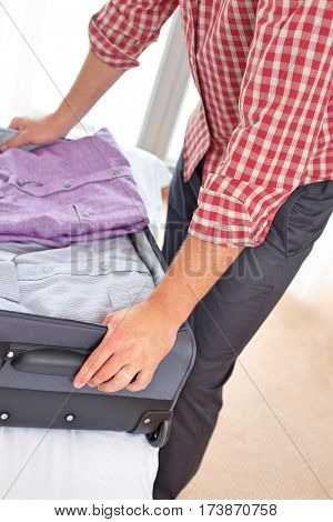 Midsection of young man unpacking suitcase in hotel room