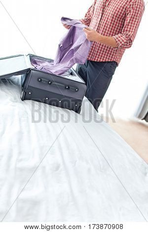 Midsection of young businessman unpacking suitcase in hotel room