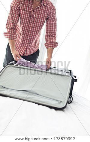 Midsection of young businessman packing luggage in hotel room