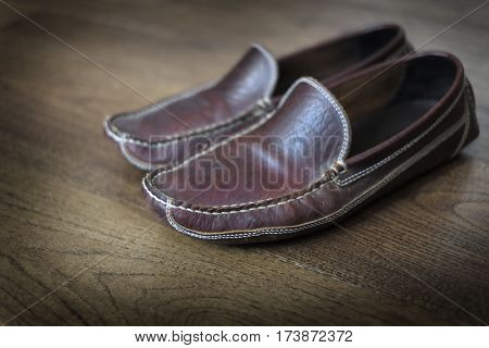Detail of comfortable leather slipper on polished wooden floor