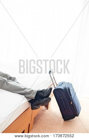 Low section of businessman relaxing on bed by luggage in hotel room