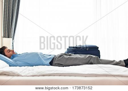 Side view of young businessman sleeping in hotel room