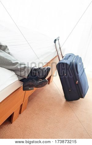 Low section of businessman lying on bed with luggage on floor in hotel room