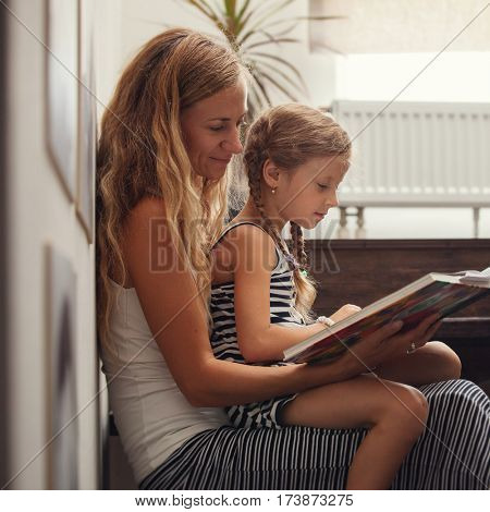 Mother with baby reading book. Female with child at home