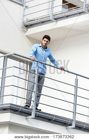 Portrait of confident young businessman standing at hotel balcony