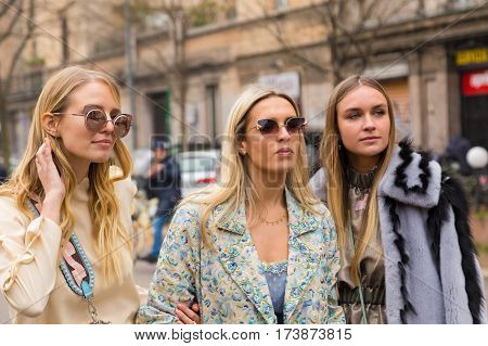 MILAN ITALY - FEBRUARY 23: Fashionable women pose outside Fendi fashion show during Milan Women's Fashion Week on FEBRUARY 23 2017 in Milan.