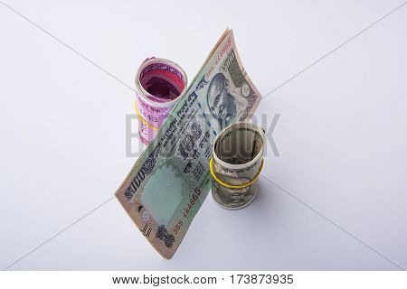 percents from indian rupees, % symbol created using arranging rolls of indian new currency notes of 500 and 2000 rupees and old 100 rupee note, selective focus