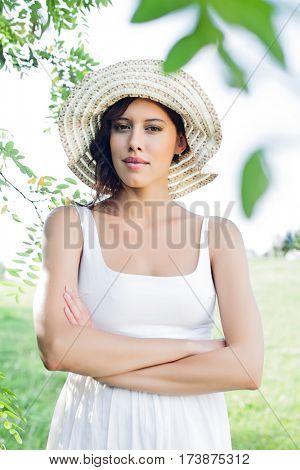 Portrait of confident young woman in sundress and hat standing arms crossed in park