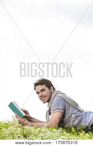 Side view portrait of young man holding book while lying on grass against clear sky